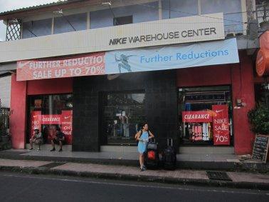 """""""Where do we need to wait for the bus?"""" - """"There, at the Nike Store Stop"""" / """"Dónde es que tenemos que esperar por el bus?"""" - """" Ahí a la vuelta, en la parada de la tienda Nike""""."""