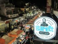 Craft beer with night-market view. // Cerveza artesanal con vista al mercado nocturno.